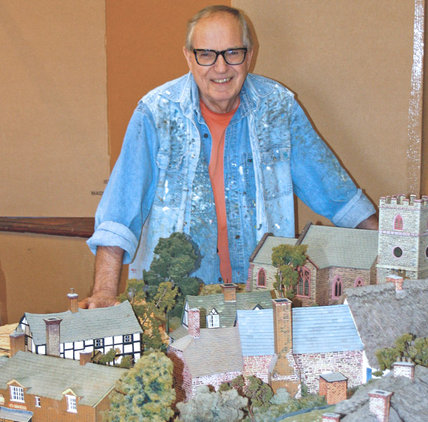 Bill Webb poses with a portion of his model of a pre-WWI English village.